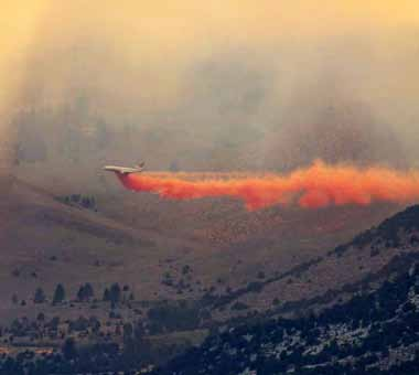 An airliner dumps retardent on a wildfire that is burning in the June Lake area near Lee Vining, Calif..