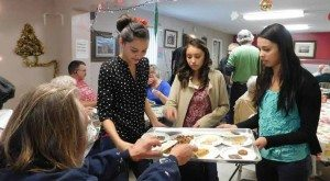 Sheri Samson Young ladies from the Seventh Day Adventist Church hand out deserts at the free Christmas Eve luncheon sponsored by local churches.
