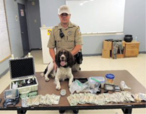 Photo courtesy of MCSO -  Mineral County officer Brad Royle and K9 Jake are shown with drug paraphernalia and cash seized after a search on June 20 at Golden Gate Petroleum.