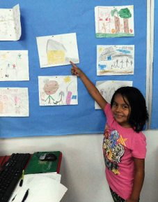 Sheri Samson -  First grade Student Sophia Galeno proudly shows her picture of family at the open house at Schurz Elementary School.
