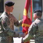 LTC Dustin G. Bishop accepting the flag from COL James L. Brown.